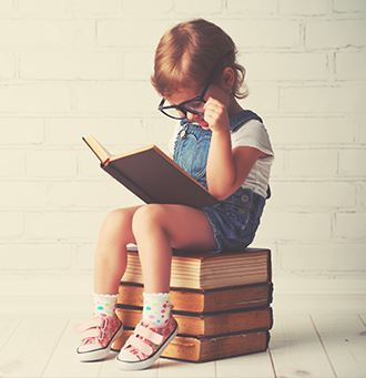 Little girl reading sitting on some books