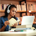 Teen doing homework in the library with her headphones and laptop