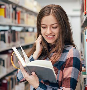 Woman enjoying reading a book among book shelves