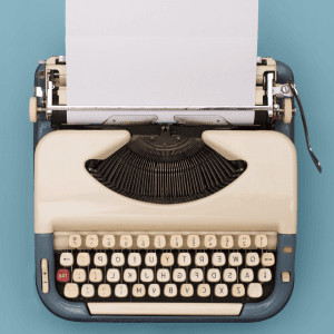 antique style type writer on a light blue background