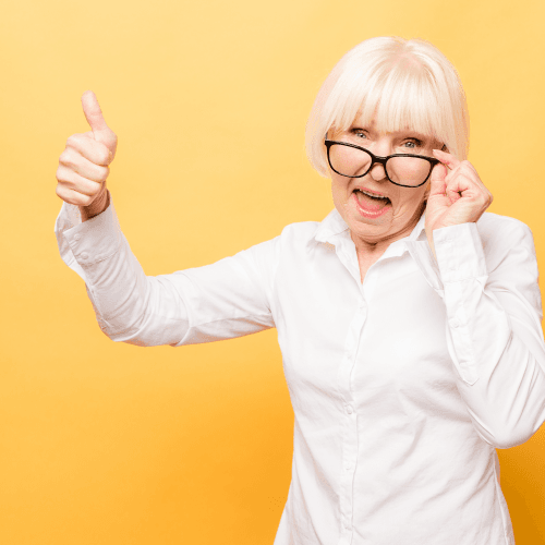 Elderly lady giving thumbs up on yellow background