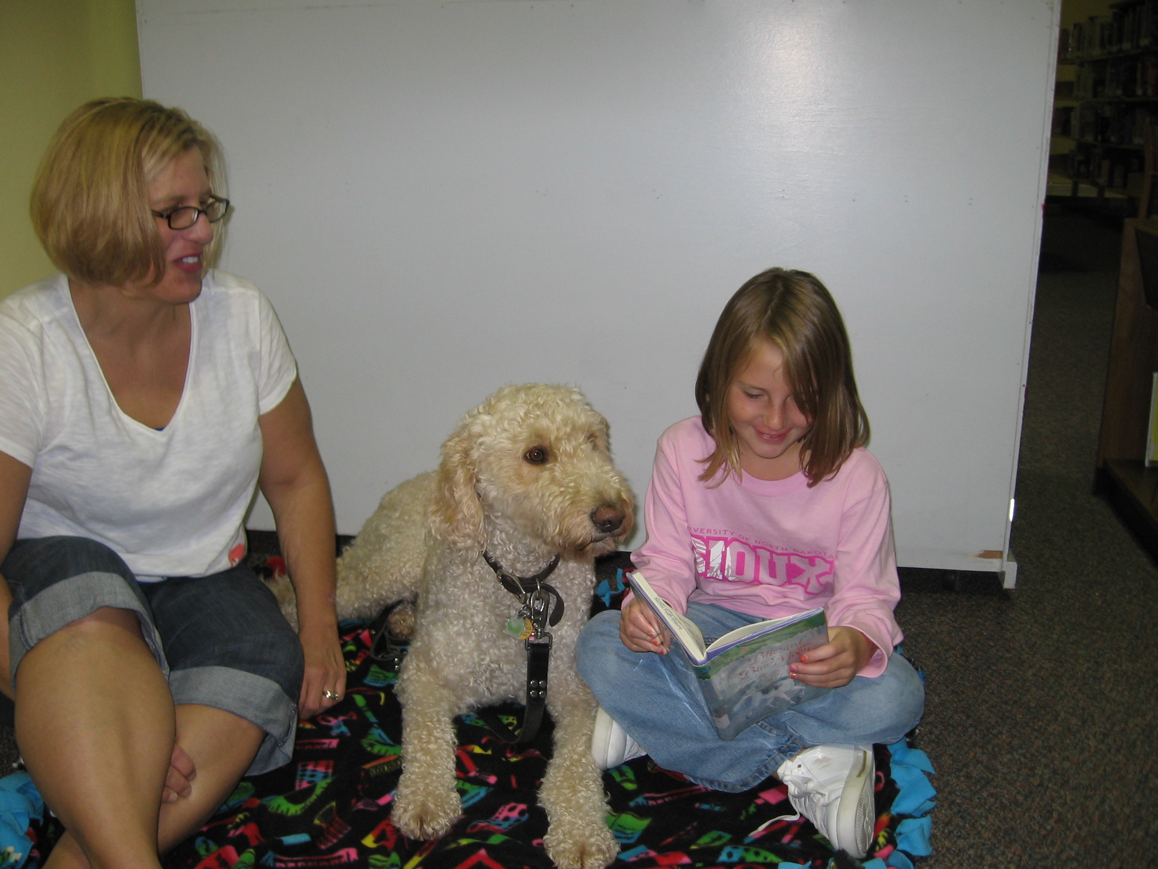 Child reading to Mudge, one of our R.E.A.D. dogs